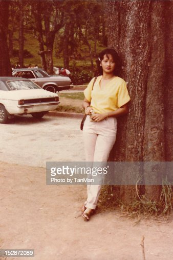 Young woman leaning on tree : Stock Photo