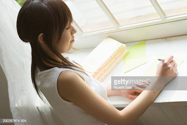 Young woman leaning on window ledge, writing on piece of paper, elevated view