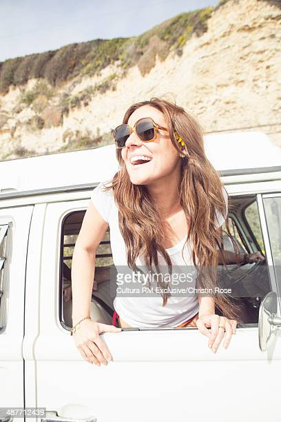 Young woman leaning out of camper van