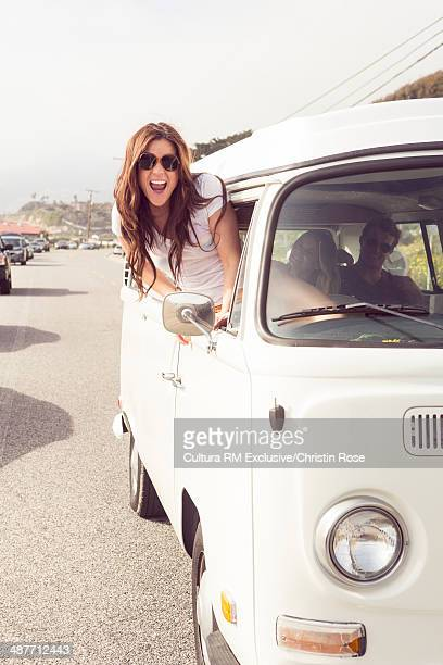 Young woman leaning out of camper van window