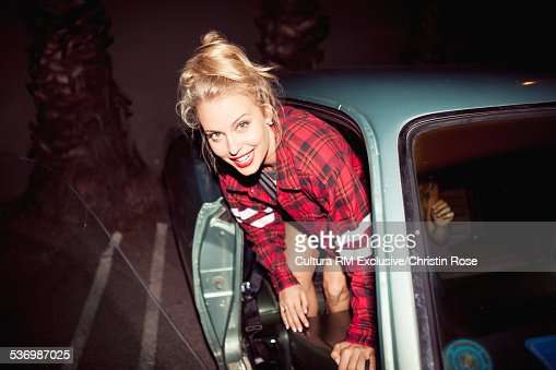 Young woman leaning out of car door