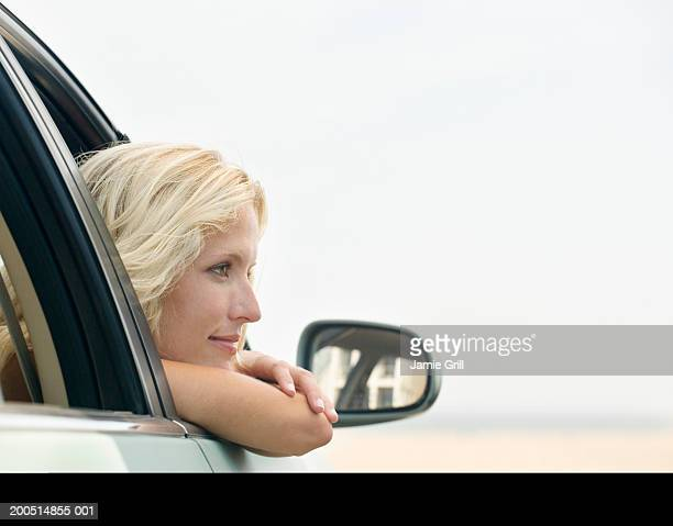 Young woman leaning out of car window, side view
