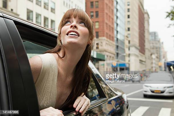 Young woman leaning out of taxicab window, looking up