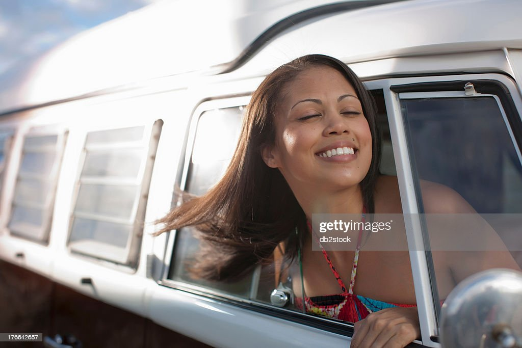 Young woman leaning out of the window of camper van, smiling : Stock Photo