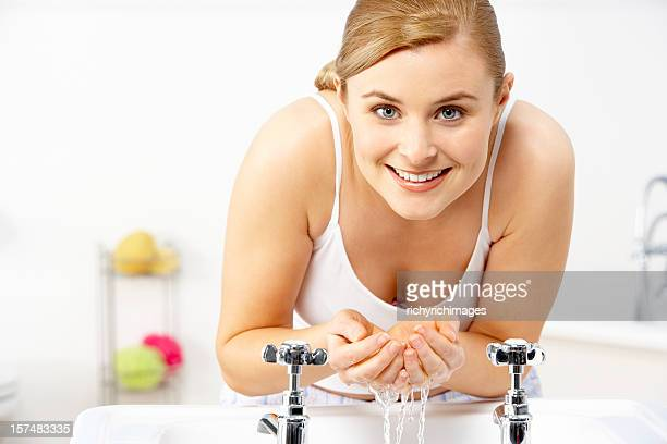 A young woman leaning over a basin and cupping water