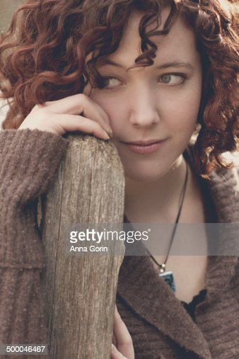 Young woman leans against fencepost, gazing away