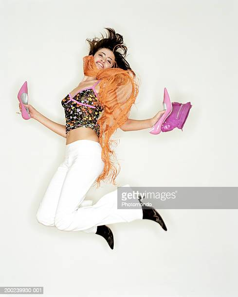 Young woman leaping, holding new shoes