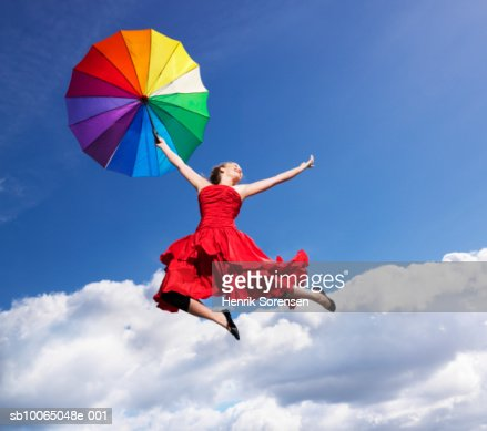Young woman leaping in air, holding umbrella, smiling : Stock Photo