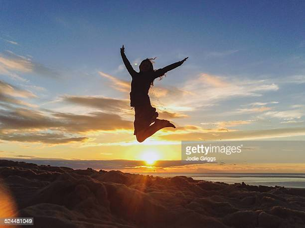 Young woman leaping into the air at sunset