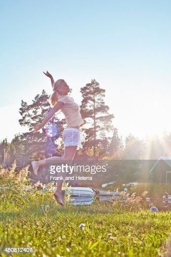 Young woman leaping next to lake, Gavle, Sweden