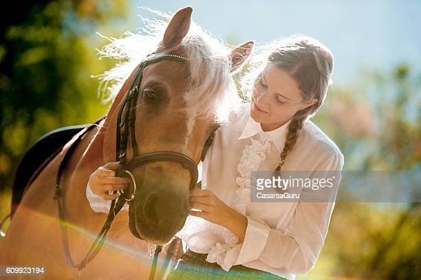 Young Woman Learning to Bridle the Horse
