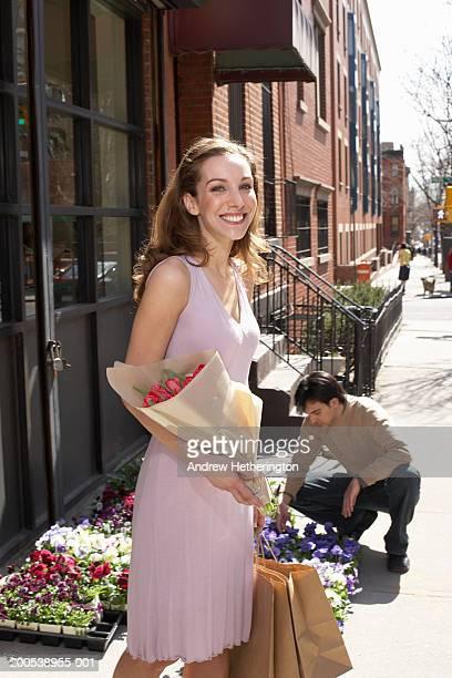 Young woman leaving florist shop