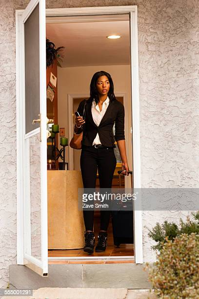 Young woman leaving house with luggage