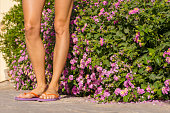 Young woman legs wearing flip flops over floral background