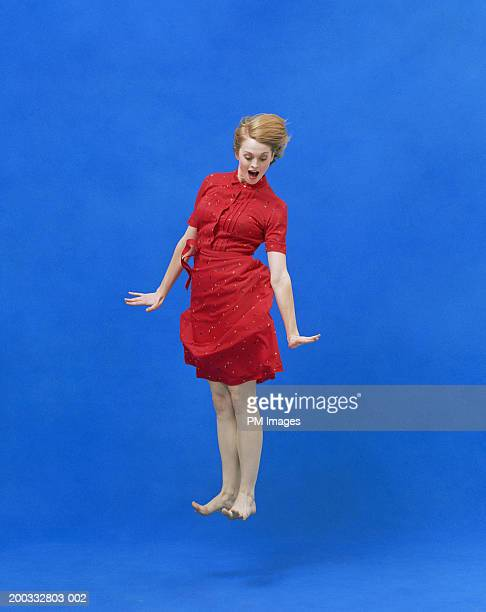 Young woman levitating with  surprise look on face