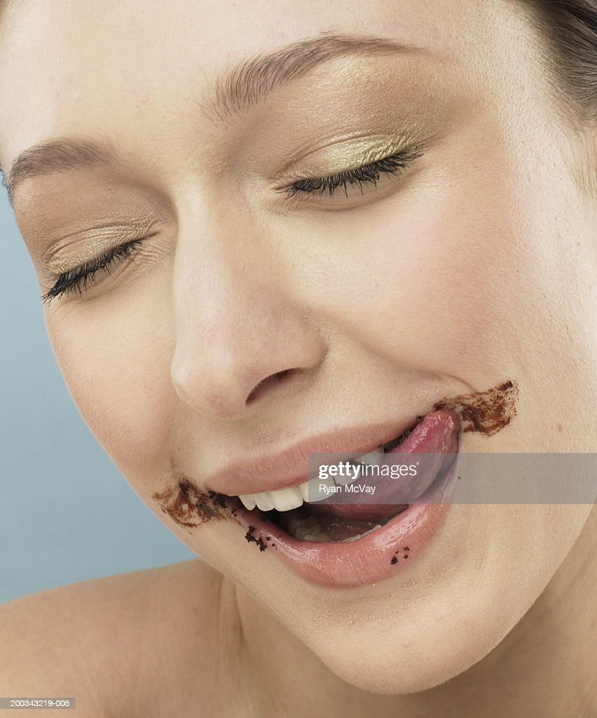 Young woman licking chocolate frosting off face, eyes closed, close-up : Stock Photo