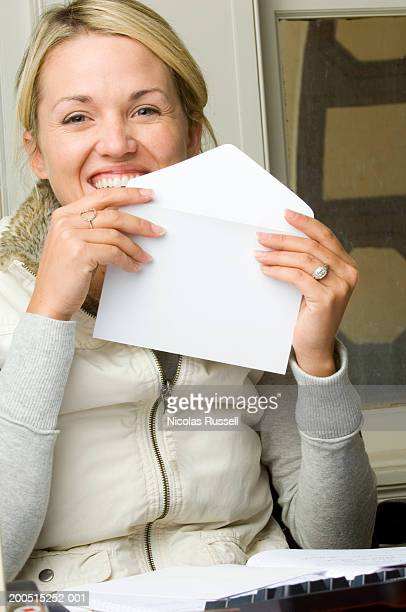 Young woman licking envelope, laughing.