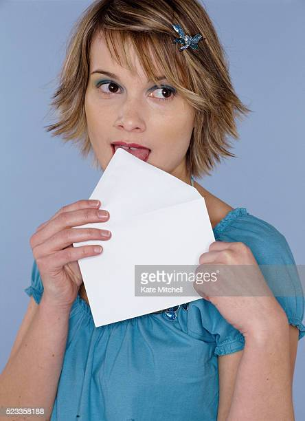 Young woman licking envelope