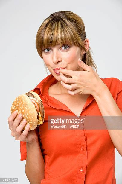 Young woman licking finger, holding hamburger, portrait, close-up