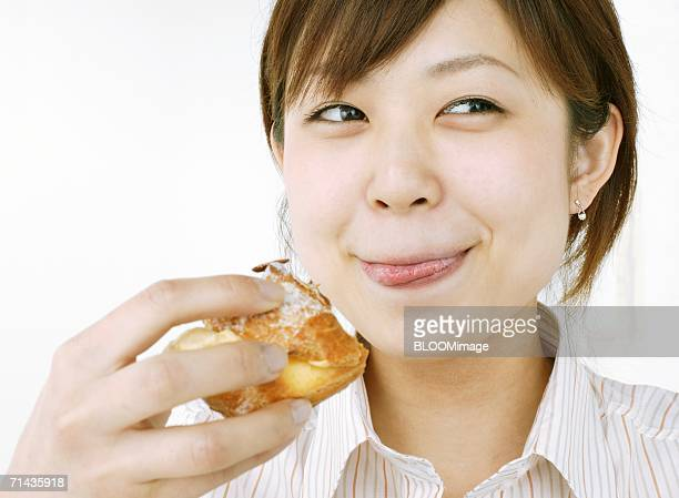 Young woman licking her lips with savory in her hand