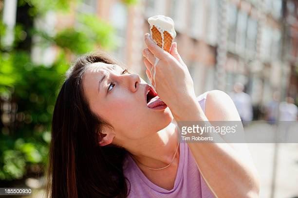 Young woman licking melted ice cream from her hand