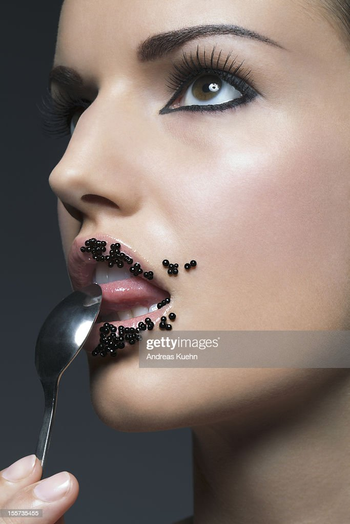 Young woman licking spoon with caviar on lips. : Stock Photo
