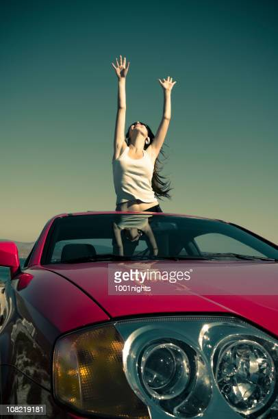 Young Woman Lifting Arms Up Standing in Car Sun Roof