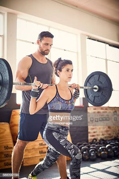Young woman lifting barbell while coach assisting her in gym