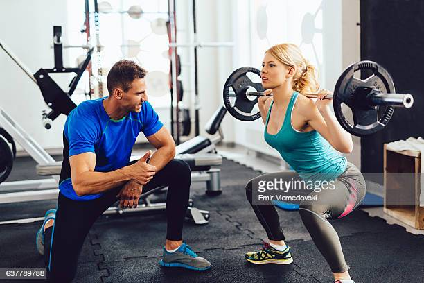 Young woman lifting barbell with her personal trainer assistance.