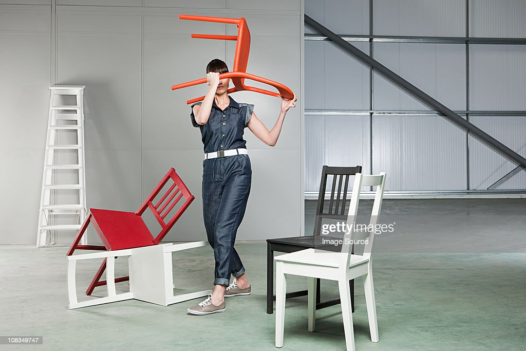 Young woman lifting chair above her head : Stock Photo