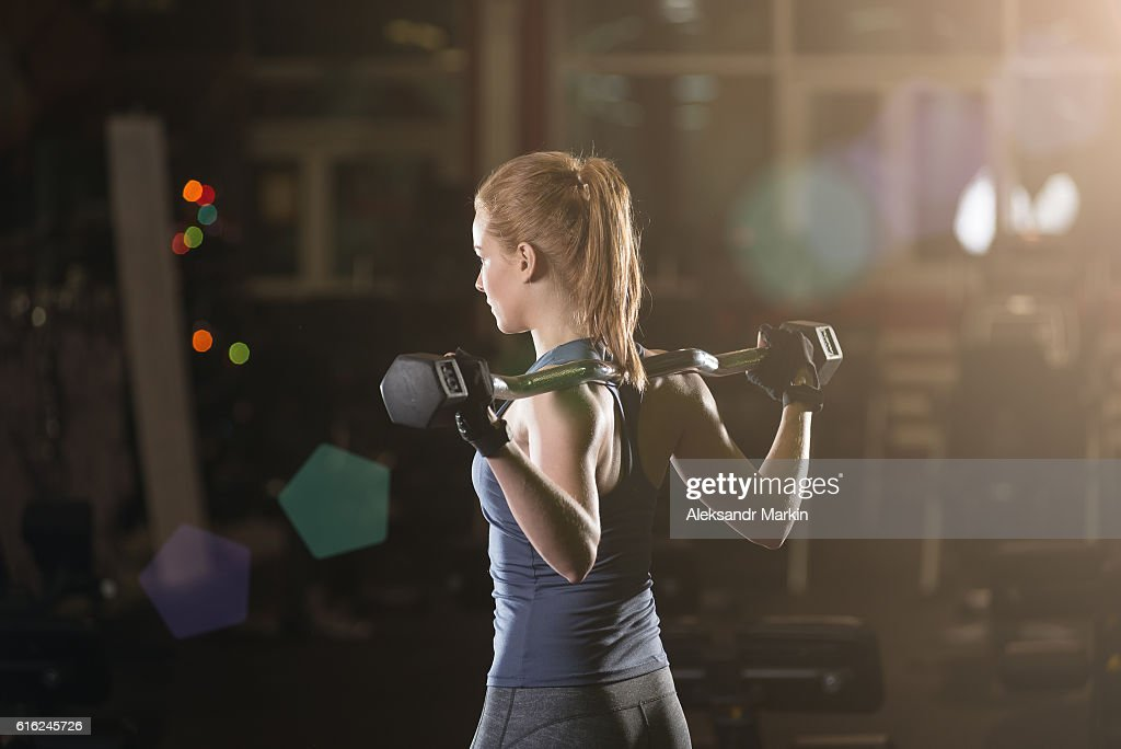 Young woman lifting the dumbbells : Stock Photo
