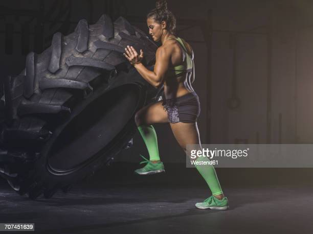 Young woman lifting up a tractor tyre
