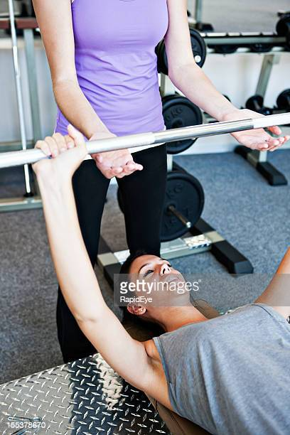 Young woman lifting weights as friend spots for her