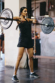 Vintage toned image using only natural light of a young woman, doing a cross training in the gym.