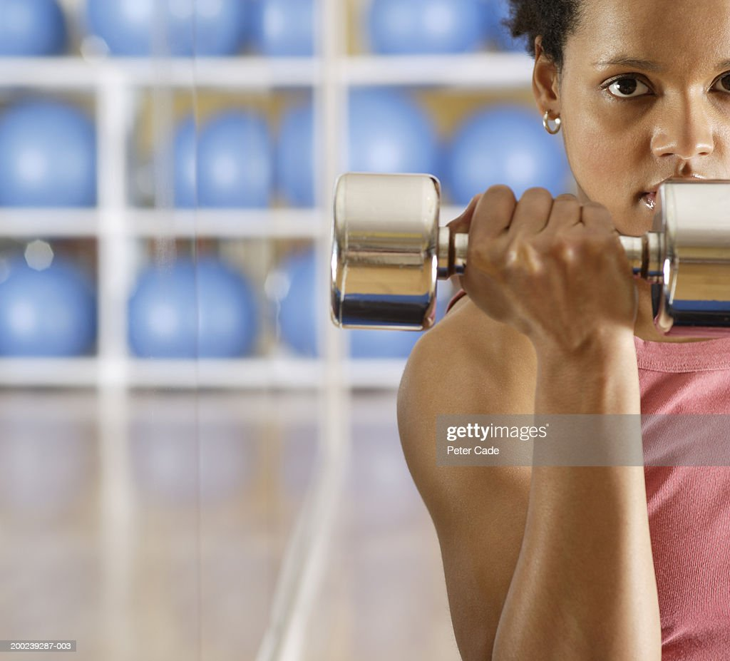 Young woman lifting weights : Stock Photo