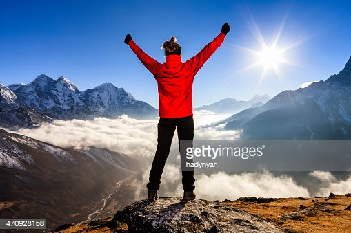 Young woman lifts her arms in victory in Himalayas