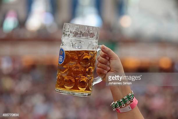 A young woman lifts up a beer mug inside Hofbraeuhaus beer tent during the opening day of the 2014 Oktoberfest on September 20 2014 in Munich Germany...