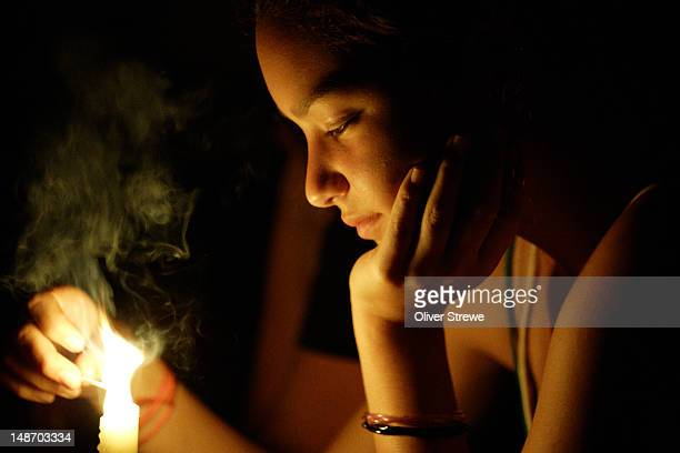 Young woman lighting candle.