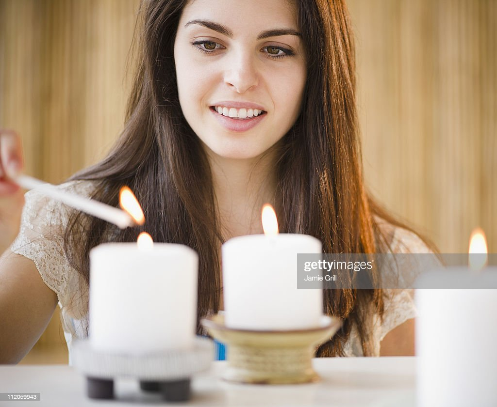 Young woman lighting candles : Stock Photo