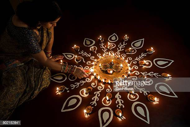 Young Woman Lighting Oil Lamps During Diwali .