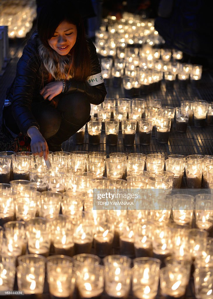 A young woman lights candles for tsunami victims at Yuriage Junior Hight School in Natori, Miyagi Prefecture, on March 10, 2013, one day before the second anniversary of the March 11 earthquake and tsunami disaster. Japan will commemorate the second anniversary of a 9.0 magnitude offshore earthquake and giant tsunami that killed 15,880 people and left 2,694 unaccounted for, mainly in the Pacific coastline of the tohoku region in the nation's northeast. AFP PHOTO/Toru YAMANAKA