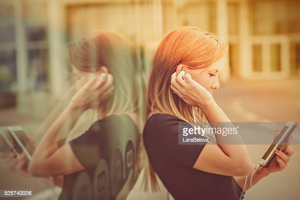 Young woman listen to music by smartphone