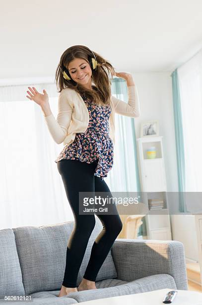 Young woman listening music and dancing on sofa