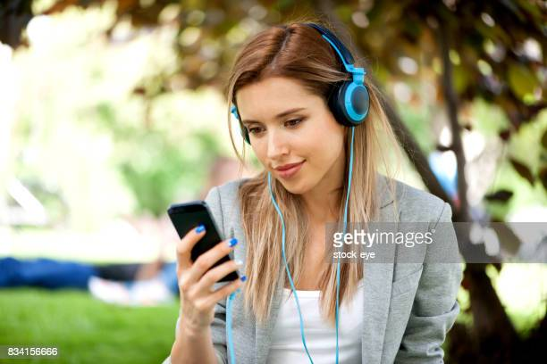 Young woman listening music on blue headphones