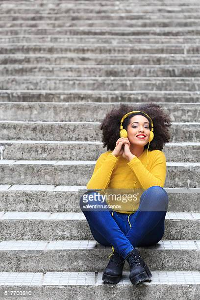 Jeune femme écoutant de la musique assis sur les escaliers