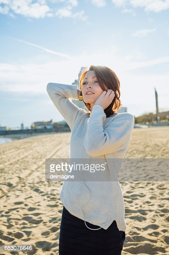Young woman listening music with headphone at the beach : Stock Photo