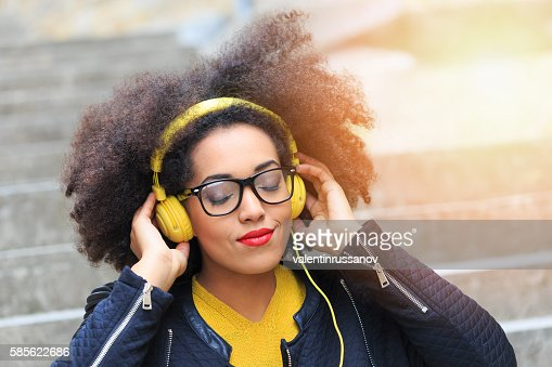 Young woman listening music with headphones on stairs