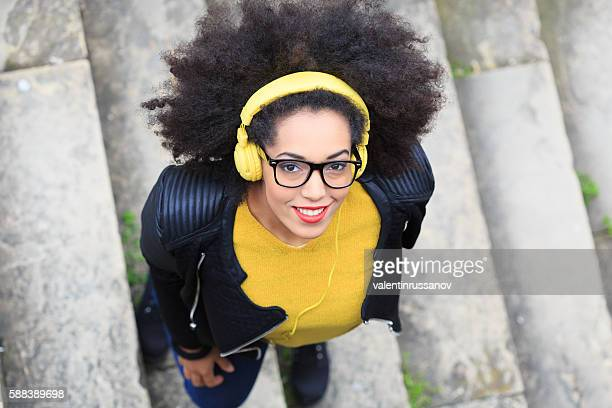 Young woman listening music with headphones standing on stairs