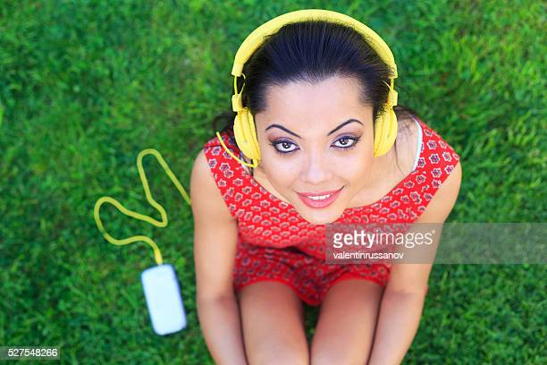 Young woman listening music with yellow headphones
