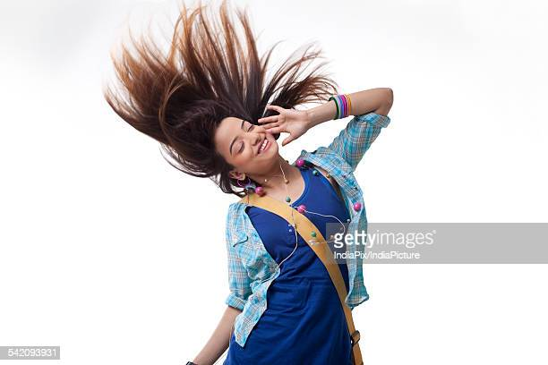 Young woman listening musing white spinning hair over white background